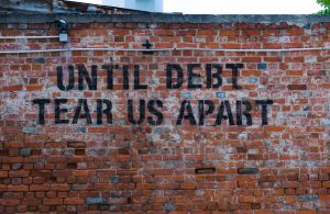 "Picture of a brick wall with the slogan ""until debt do us part"""